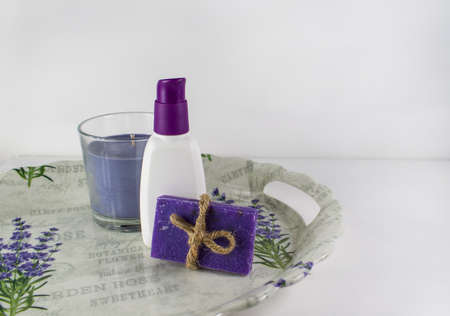 Flat lay spa bath on white wooden background, top view products for hygiene. Candle, handmade soap lavender and tube
