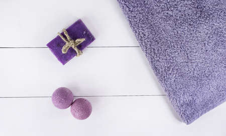 Flat lay spa bath on white wooden background, top view products for hygiene. Bombs and soap from lavender with towel. Фото со стока