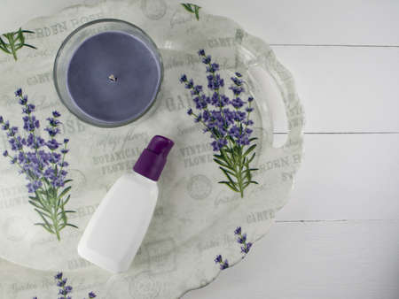 Flat lay spa bath on white wooden background, top view cosmetic product. Candle lavender and tube cream Фото со стока