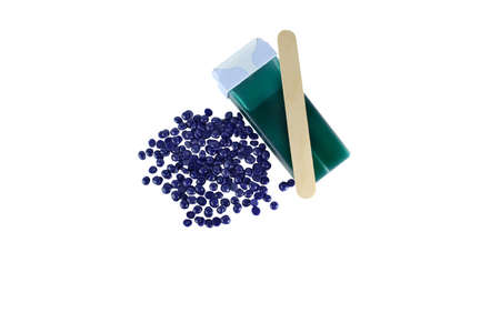 Top view hair removal depilation concept. Green aloe wax cartridge and violet granules with wood spatula isolated on white background. 免版税图像
