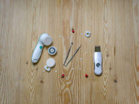 Cosmetic flat lay with electric and ultrasonic scrubbers, spoon and loop for cleansing face on wooden background.