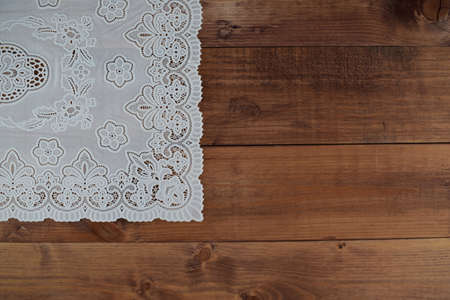 White lace napkin on brown wooden background. Vintage background with white crochet lace.