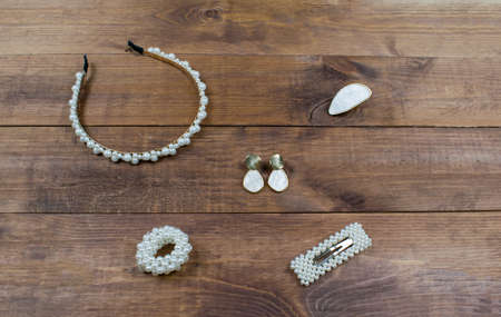 Flatlay set jewelry pearls accessories on wooden brown background. Hair band, ring, earrings, scrunchy and hairpin for hair.