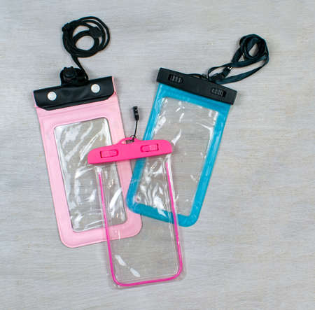 Waterproof phone bags, cases, covers with laces isolated on wood grey background. Plastic PVC waterproof case for smartphone, zip lock bag protect. Pink, blue and crimson color. Thai New Year or Songkran water festival in Thailand.