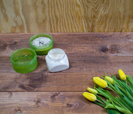 Flatlay Spring Easter bouquet of yellow tulips with cosmetic products on brown wood background. Set of scrub, sea salt, gel aloe, cream for face and body. Top view beauty flat lay. Foto de archivo