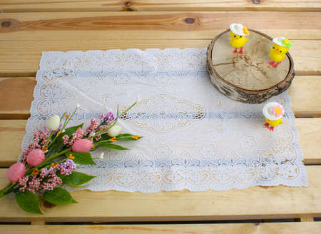 Easter holiday. White lace napkin, chickens toys on slice and bouquet of spring flowers with colorful eggs on yellow wood background. Vintage background with crochet lace. Home interior top view. 版權商用圖片
