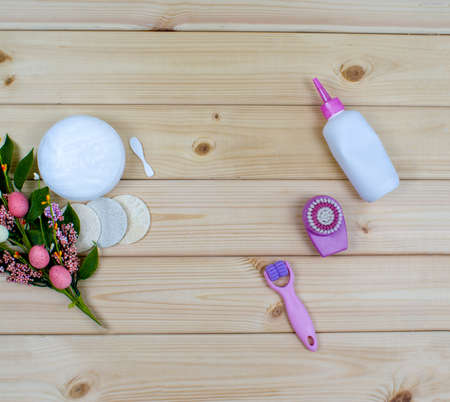 Top view beauty tools and cosmetic products for cleansing face or body on wood background. Flowers, sponges, brush, roller, cream, lotion, scrub.