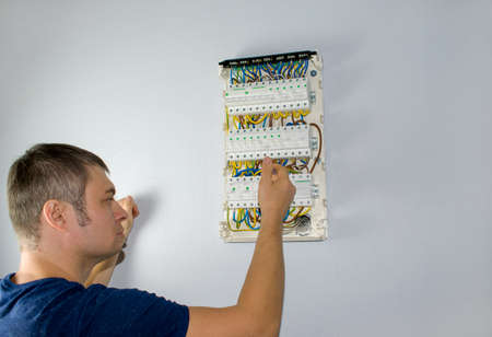 A male electrician works in a switchboard with an electrical connecting cable, fuses. Connects the equipment with tools, the concept of complex work. 版權商用圖片