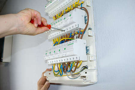 A male electrician works in a switchboard with an electrical connecting cable, fuses. Connects the equipment with tools, the concept of complex work.