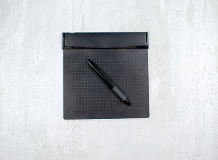 Black graphic digital tablet with pen for illustrators and designers, isolated on a light wood background.