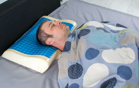 Men lying on bed with orthopedic pillow. Healthy posture concept. Latex pillow with memory foam effect, hydro gel layer. Medical treatment pillow for sleep under the head with a recess under the neck.