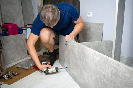 Young man screwing boards with bolts using electric screwdriver collecting furniture, hands closeup. Assembling gray wooden case wardrobe on floor at home house.