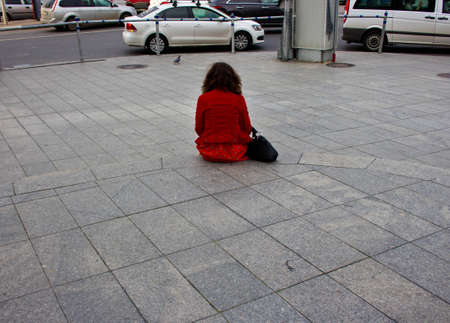 dullness: A girl in red coat sitting alone