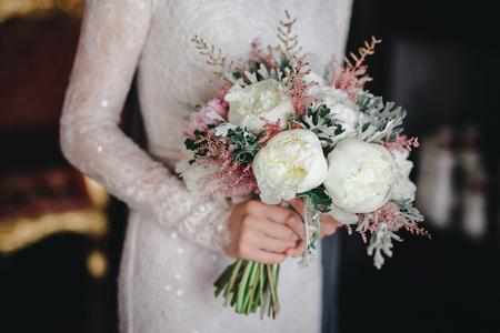 Hochzeitsblumenstrauß mit weißen und rosa Blumen in den Händen der Braut