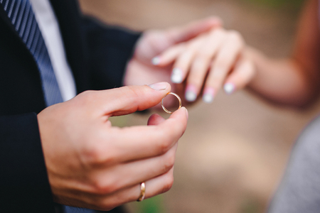 groom wears the ring bride Stock Photo