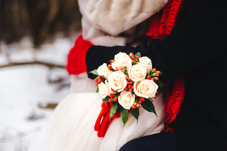 affable: Beautiful winter wedding bouquet. Bridal bouquet with cones, cotton and spruce branches. The bride holds a wedding bouquet next to the groom.