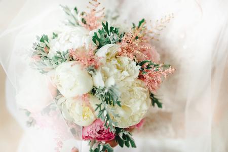 bruiloft boeket met witte en roze bloemen in de handen van de bruid