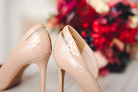 beige wedding shoes with bouquet of flowers
