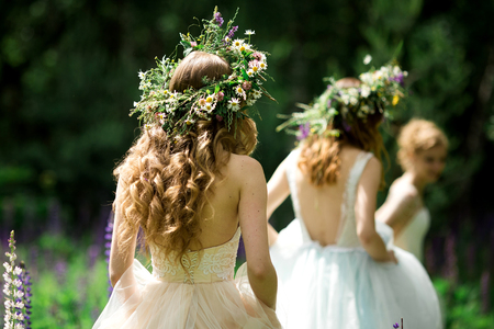 Wedding. The bride in a white dress standing and embracing bridesmaids Standard-Bild