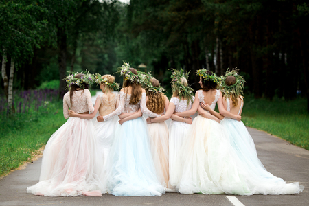 Wedding. The bride in a white dress standing and embracing bridesmaids Фото со стока