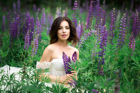 Beautiful young woman in white dress in lupine field