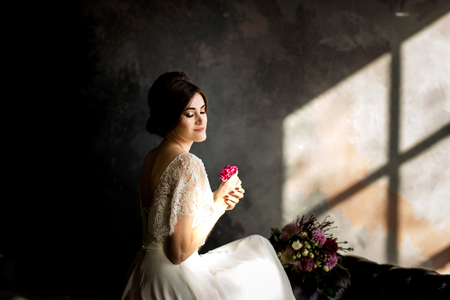 Bride in beautiful dress sitting on chair indoors in dark studio interior like at home.