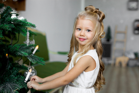 Merry Christmas and Happy Holidays. little girl decorates a Christmas tree.