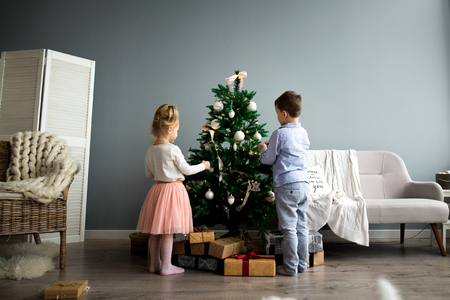 Cute girl and boy dress up the Christmas tree. Merry Christmas and Happy Holidays.