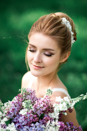 Beautiful girl hands with a branch of a blossoming apple tree. Young beautiful blonde woman in blooming garden. Bride.
