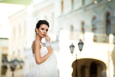 fashion photo of beautiful woman with dark hair in luxurious wedding dress posing outdoor. Foto de archivo