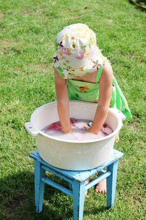 toddler girl washes clothes and underwear in a basin outdoor as an adult