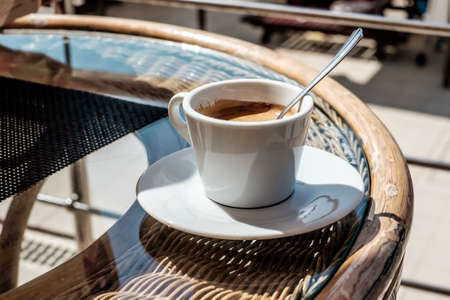 a cup of coffee on a glass table. summer cafe Stock Photo