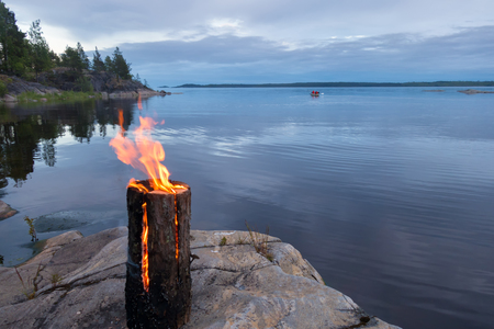 A fire from one log burns on the lake shore in the evening. In the background, you can see a boat and a stone cape, covered with forest.