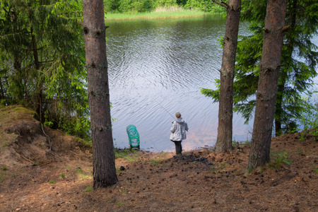 A woman is standing on the shore of a lake and is fishing. She has a fishing rod in her hands.