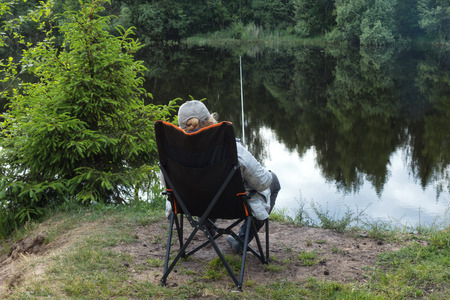 A woman sits in an armchair on the shore of a pond and catches fish. In her hands a fishing rod.