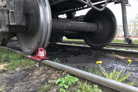 The brake shoe is placed under the wheel of a railway car. A dandelion grows near the rail. Фото со стока