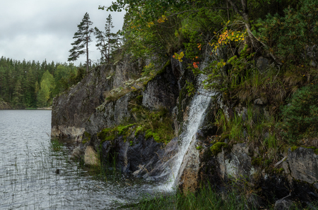 A small waterfall flows into the lake from a rocky shore. Ladoga lake. Karelia. Russia.