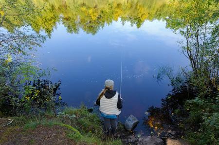 Une femme de pêcheur se tient avec une canne à pêche sur la rive du lac. Dans l'eau, les reflets des arbres de la rive opposée sont visibles.