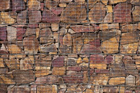 gabion mesh: Wall of stone, reinforced with a grid of metal. Gabion. Background. Texture. Stock Photo