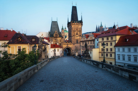 Charles Bridge in Prague in the early morning. View of Malostranska Tower and Judithin Tower. In the background on the mountain you can see Prague Castle.