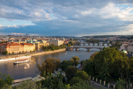 View of the city of Prague and bridges over the river Vltava in the evening.  The city is lit by the setting sun