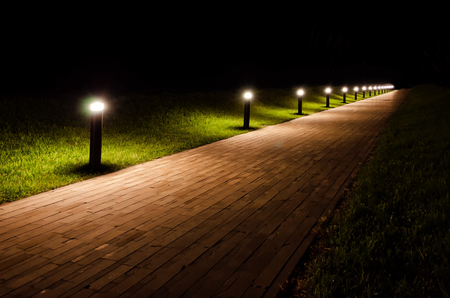 Night landscape of the park. The path is covered with beige tiles and is lit by flashlights. Around the path there is a lawn with green grass. Фото со стока