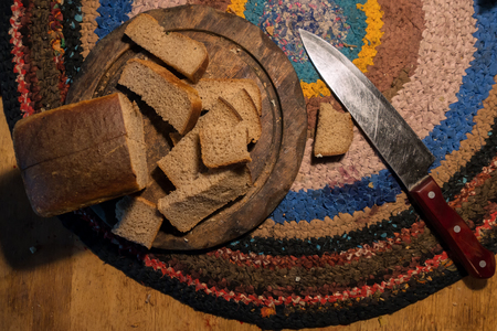 Inaccurately cut bread lies on the cutting board. Under the plank on the floor is a homemade rug made from multi-colored pieces of fabric. Фото со стока