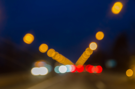 Light headlights, signal lights of cars and streetlights on the evening road. Bokeh. Background.