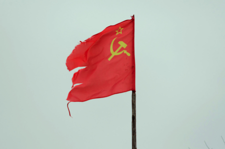 Old shabby red flag of the USSR on the flagstaff. The flag depicts a star and a sickle and a hammer. Фото со стока