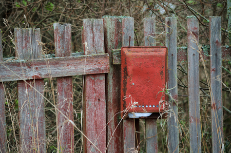 Red mailbox on the old village fence.  There is mail in the mailbox. In the foreground there are thin high stems of grass.