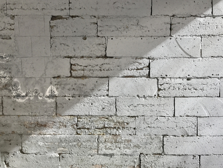The brick wall is painted white. The wall is divided into light and shadow parts along the diagonal. Background. Texture. Фото со стока