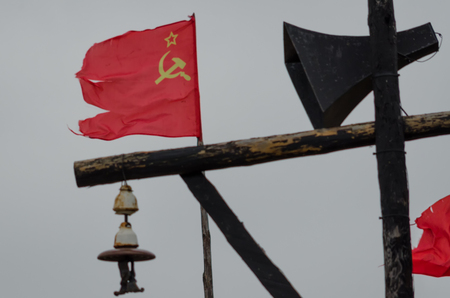 An electric pole with an old loudspeaker. In the background, the flag of the Soviet Union is visible. Фото со стока