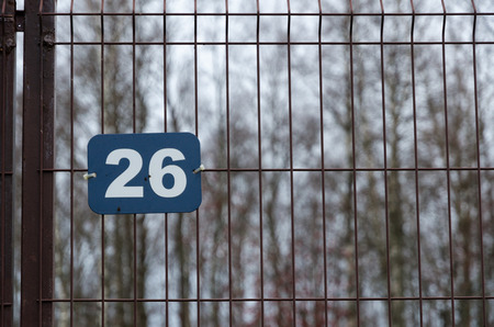 Blue rectangular plate with white number 26. The plate is attached to a white fence made of metal mesh. In the background, you can see the crowns of trees without leaves. Background. Texture.
