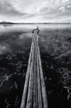 A long decking of logs goes far into the lake. At the far edge of the deck, a man sits and catches fish. Black and white. Background. Vertical.